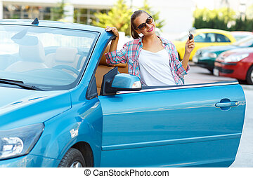 Woman in sunglasses standing near convertible with keys in...