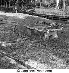 black and white, old stone bench in the park at morning