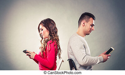 Couple using mobile phones not talking Conflict - Couple...