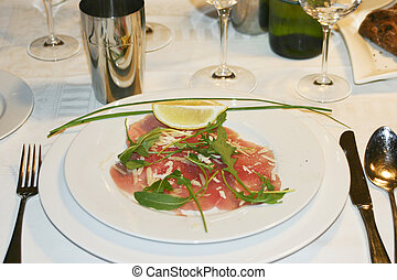 Plate of carpaccio on set dinner table - Luxury table...