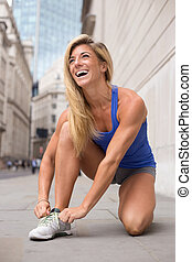 tying shoe laces - happy woman tying her laces while out...