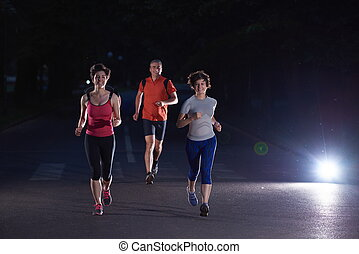 people group jogging at night, runners team on early morning...