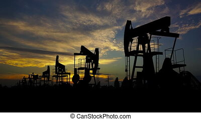working oil pumps against timelapse sunset - working oil...