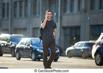 Young man on phone crossing street