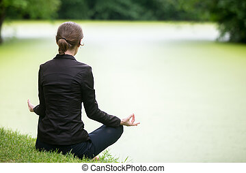 Young woman meditating on lake - Young attractive woman...