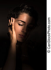 Young beautiful woman in dark shadow and ray of light