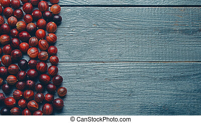 Berries gooseberries on wooden background, space for text in...