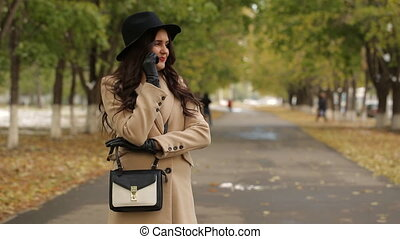 Happy girl walks in autumn alley and talking on the phone