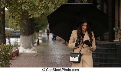 Girl under umbrella walking and typing a message