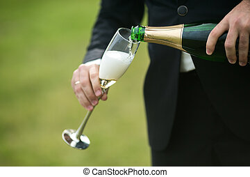 Groom pours a glass of champagne for the bride