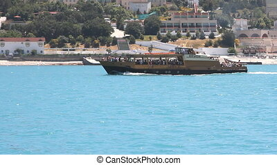 Pleasure boat floats on the sea at sunny day