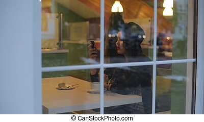 Young beautiful woman sitting in cafe and read message