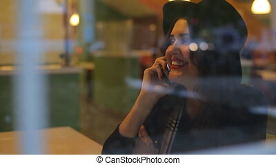 Young beautiful woman sitting in cafe and talking on the phone