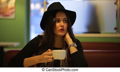 Young woman sitting in cafe and dreams of a beautiful