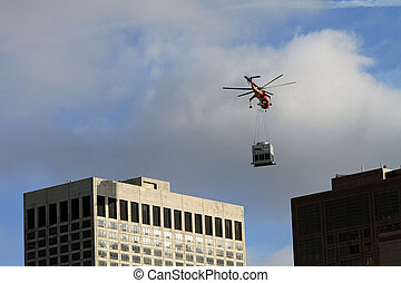 A helicopter placing some heavy equipment on the roof of an...