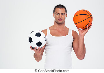 Handsome man holding basketball and soccer ball - Portrait...