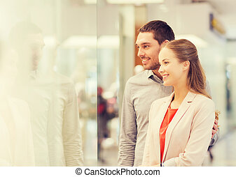 happy couple looking to shop window in mall - sale,...