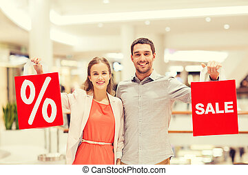 happy young couple with red shopping bags in mall - sale,...