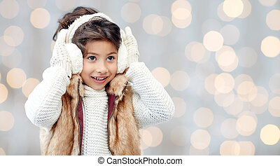 happy little girl in earmuffs over holidays lights - winter,...
