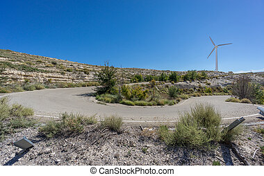 U-shape curved road and wind turbine against sun - Wide...