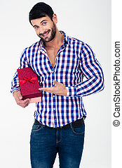 Smiling casual man holding gift box - Portrait of a smiling...