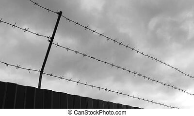 Timelapse of barbed wire against sky. - Black and white...