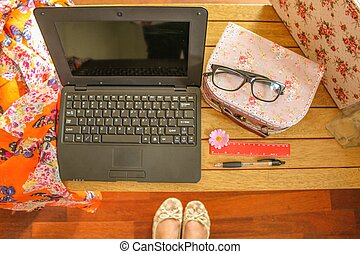 Feminine workspace with glasses, laptop and cases from a...