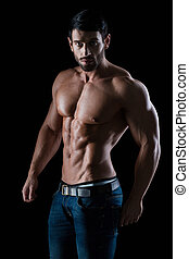 Portrait of a fitness man with muscular body posing on black...