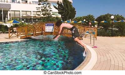 Young man does front flip dive into pool. - Front flip in...