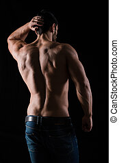 Back view portrait of athletic man with posing on black...