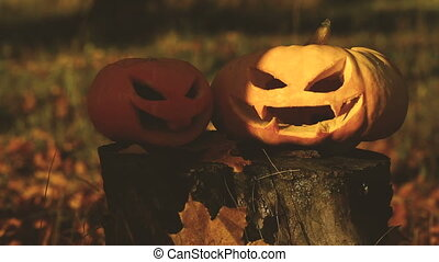 Two scary pumpkin lantern on a stump - Two scary pumpkin...