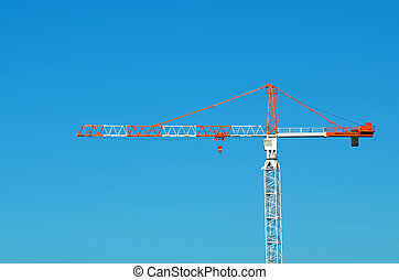 Profile of a red and white Tower crane against blue sky...