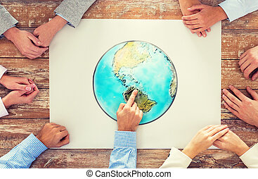 close up of hands with globe picture at table