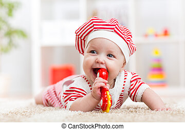 Cute baby in hat on the carpet having fun - Playful baby kid...