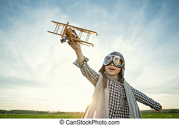 Aviator - Little boy with wooden airplane outdoors