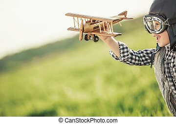 Pilot - Boy with wooden airplane in the field