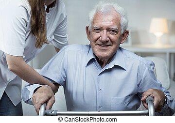 Nurse is helping elder man to get up
