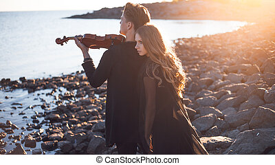violinist and girl, young man plays on the background of sea...