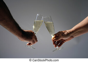 Honeymoon - bare female and male arms toasting with glasses...