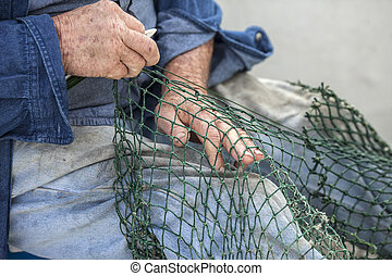 mending nets - Hands of commercial fisherman mending nets