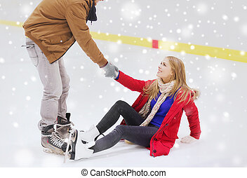 man helping women to rise up on skating rink - people,...