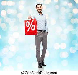 smiling man with red shopping bag over blue lights - people,...
