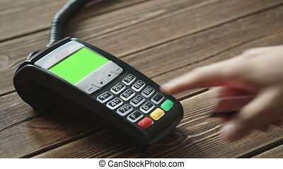 Hand swiping credit card on POS terminal - Man's hand...