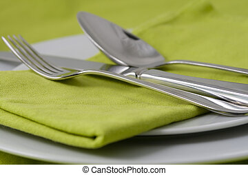 tableware on green - fork, knife and spoon on green napkin...