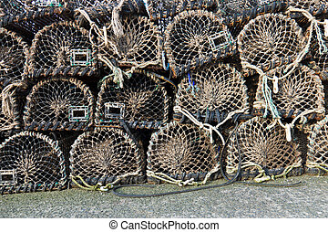 Group of old wooden lobster traps stacked on wharf - Group...