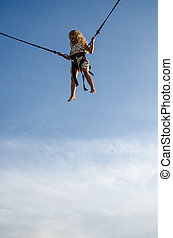 girl jumping into skies - cute little girl with long blond...