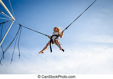 kid on jumping attraction - little girl jumping up into the...