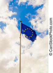 European union flag waving against a cloudy sky