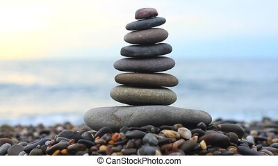 Stack of stones at sunrise and sea splash