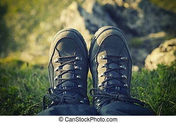 Trekking boots in the mountains against precipice, travel...
